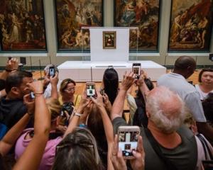Touristes agglutinés devant la Joconde, tous en train de la photographier avec leur smartphone