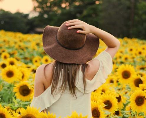 Femme au chapeau dans un champs de tournesols